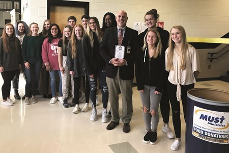 Cherokee HS Principal Todd Miller stands with the school's Chick-fil-A Leadership Academy students who proposed the idea of the MUST partnership food pantry.