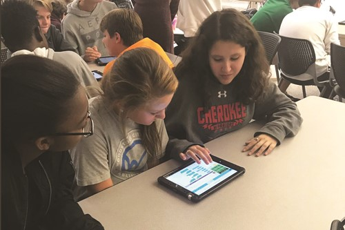 Freedom MS students, from left to right, Jameilah Grierson, Savannah Read and Karen Quintino work together on a coding exercise using a tablet.