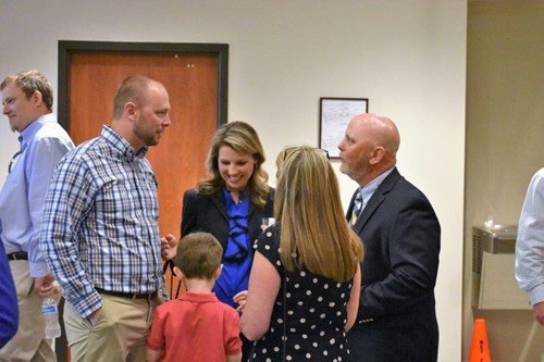 Sandi Harrison, center, new Hasty ES Fine Arts Academy assistant principal, and her husband, David, left, who is a River Ridge HS teacher, and son, Will, greet David Dyer, new River Ridge High School assistant principal and his wife, Jill, who is a teacher in Blue Ridge.