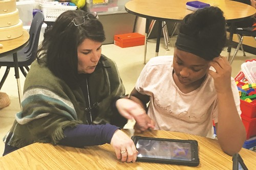 Oak Grove ES Fine Arts Academy fifth-grader Faith Day talks code with Cherokee County School District Supervisor of Instructional Technology Dr. Shannon Carroll.
