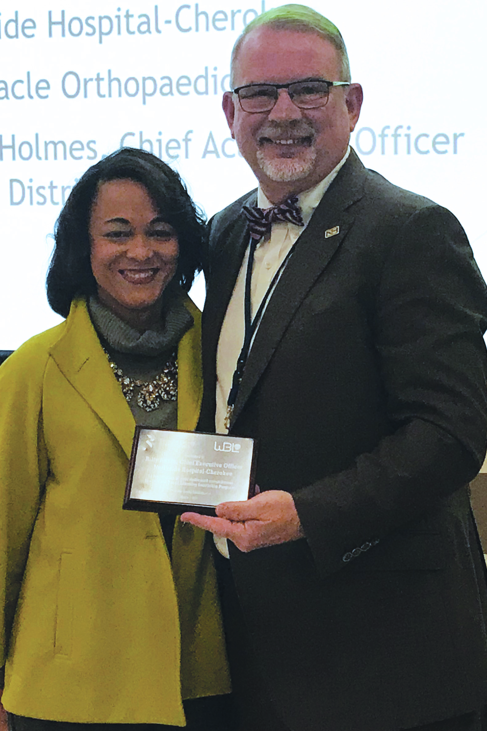 CCSD Chief Academic Officer Dr. Nicole Holmes presents an award of appreciation to Northside Hospital Cherokee CEO Billy Hayes