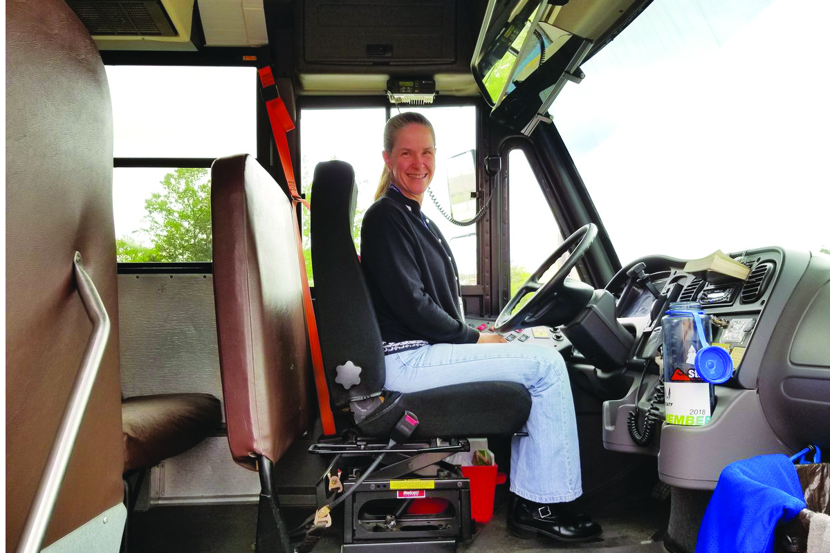 bus driver seated behind wheel of bus