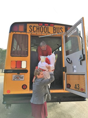 man hands basket to woman from back of school bus