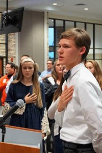 student stands and leads the Pledge