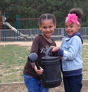2 students holding a watering can in the garden