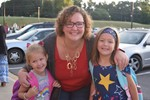 Mom is hugging her 2 students outside school