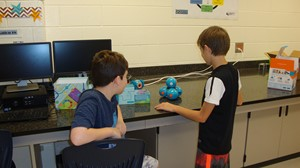 Photo of 6th Grade E.T. Booth students programming a robot purchased by the PTSA.