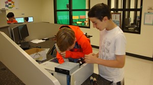 Photo of 7th grade ET Booth students reassembling a desktop computer from parts provided by the community