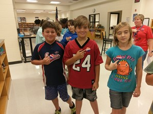 Photo of three students showing off the stickers they received to let others know they voted.