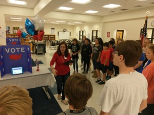 Photo of Ms. Graves, Media Specialist, giving instructions to students prior to their voting.
