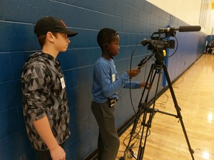 Photo of ET Booth Middle 7th and 6th grade students operate a camera during the live streaming of a basketball game on the world wide web.