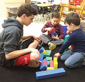 Photo of a Teasley Middle School student reading with two preschool students.