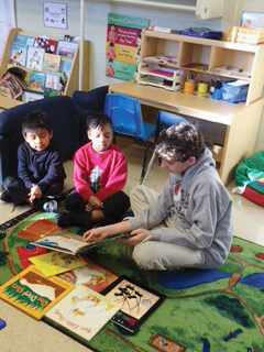 Photo of a Teasley Middle School student reading with preschool students.