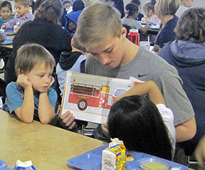 Photo of a Teasley Middle School student reading to two preschool students in the school cafeteria.