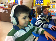 Photo of a preschool student wearing headphones and using a computer.