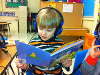 Photo of a preschool student wearing headphones and using an interactive book.