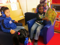 Preschool students reading in a children's reading area.